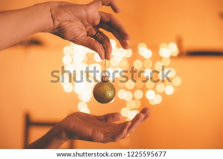 The girl is holding a small shiny green Christmas ball in the background of bright garlands #1225595677