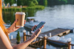 The girl is holding a smartphone with coffee in her hands. In the background water embankments with a pleasure boat