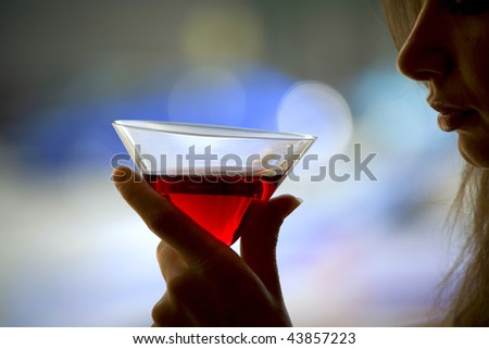 The girl is holding in his hand a glass of alcoholic beverage, red wine in glass - stock photo