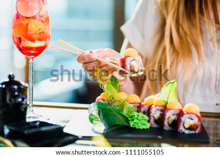The girl is holding the sushi nigiri rolls in hand whith manicure and cocktail on a beautiful blured restaurant background. sushi with tuna