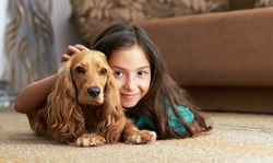 The girl is lying in the floor with the dog