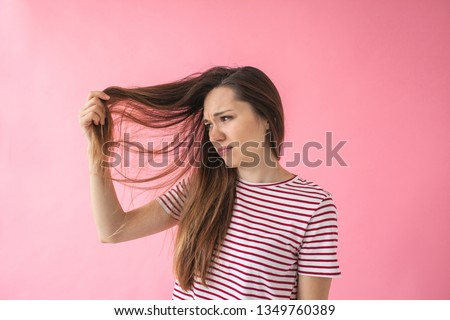 The girl is not happy with her hair and shows split ends or dandruff or dry hair or other problems.