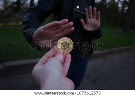 The girl is offered a gold bitcoin but she refuses, showing the appropriate gesture. Concept: disappointment in cryptocurrency, distrust of bitcoin, bitcoin fall.