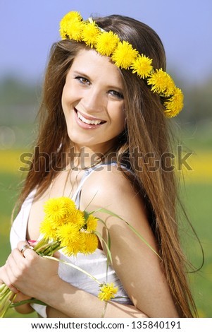 The girl is on the field and in the hands holding a bouquet of dandelions