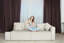 The girl is resting on the couch In the interior of the apartments