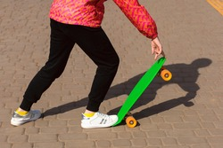 The girl is riding a skateboard or penny board in the park. The child is dressed in bright clothes and is learning to ride a green penny board. Emphasis on the skate and the legs of a girl riding it