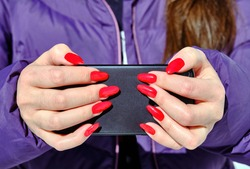 The girl is secretly filming with a smartphone camera, hiding the lens between her fingers for secrecy; concept of secrecy, stealth and pursuit