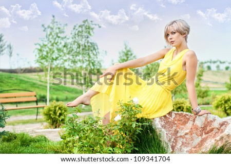 The girl is sitting on a stone in the park