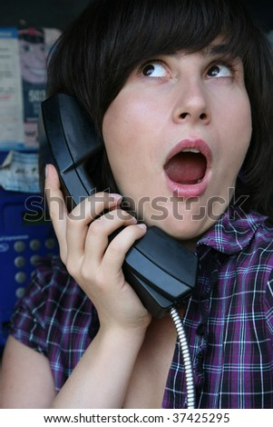 The girl is surprised by news heard on phone #37425295
