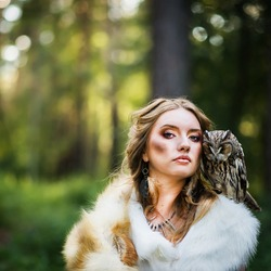 The girl is the huntress in the forest with an owl on her shoulder