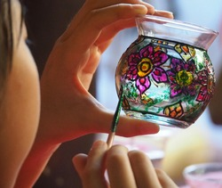 The girl is using a paintbrush painted on a glass.