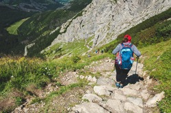 The girl is walking along the path over the precipice. Extreme and dangerous hiking trail. Picturesque  tourist place in mountain. Huge rocks of the Small Giewont peak in the Tatra Mountains, Poland.