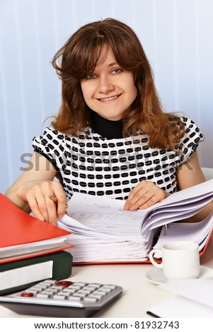 The girl is working with financial documents at a desk - stock photo