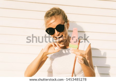 The girl licks her fingers soiled thawed popsicle. Cheerful and cheerful emotions, summer vacation and hot summer. Frozen desser quickly melts in the sun outdoors. #1453485278