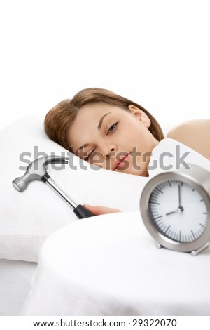 The girl lies in bed and is going to break a hammer an alarm clock