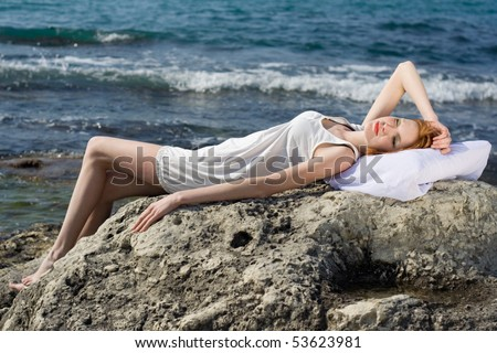 The girl lies on a pillow on a rock near the sea