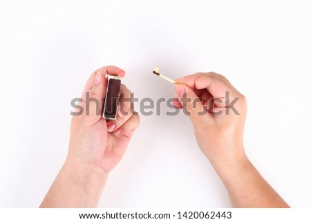 The girl lights a match from a box of matches on a white background. Top view.