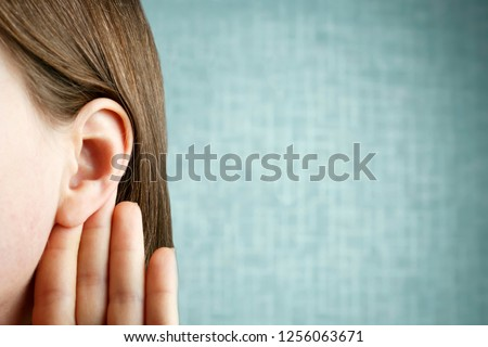 The girl listens attentively with her palm to her ear, close-up, indoors, the news concept