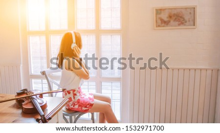 The girl listens to music through her headphone on a chair by the window in the music practice room alone in the morning. The girl sat alone in the room alone to listen to the music from the headphone #1532971700