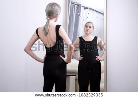 the girl looks at her reflection in the mirror. Think yourself fat. the causes of anorexia and bulimia Сток-фото ©