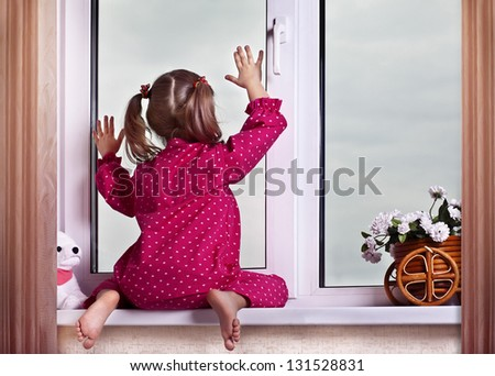The girl looks out of the window