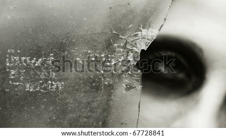 the girl looks through the broken glass