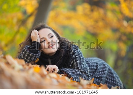 The girl lying on the ground in autumn park