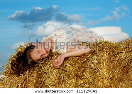 The girl lying on the straw bale on blue sky