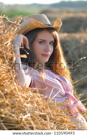 The girl near a haystack in a cowboy's hat - stock photo