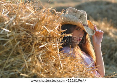 The girl near a haystack in a cowboy's hat