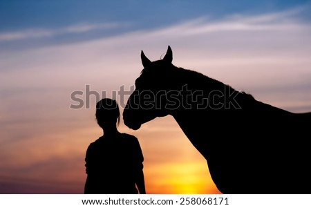 The girl near to a horse standing in front of a beautiful sunset. Silhouette of a woman and a horse\'s head.