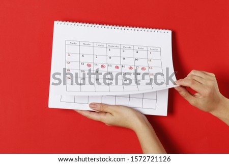 The girl notes on the calendar the days of ovulation on a red background. Ovulation concept. menstruation concept.