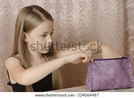 the girl of 9 years opens a ladies\' handbag which faces it.