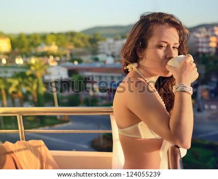 The girl on a balcony drinks coffee