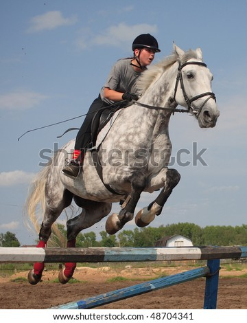 The girl on a grey horse jumps through a barrier