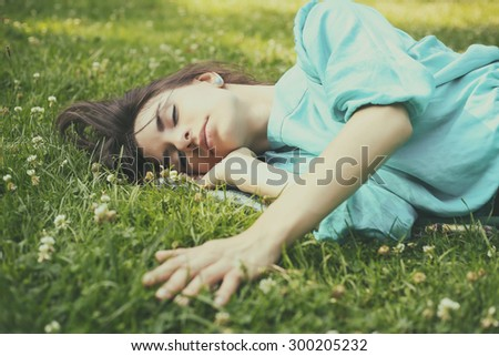 The girl on the lawn. Rest in nature. Sleeping on the lawn, to dream. Dreamer. Stroking the grass. Relaxation, bliss, rest. Sweet sleep. Sweet dreams.