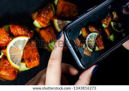 The girl on the phone takes pictures of a roasted pumpkin bruschetta