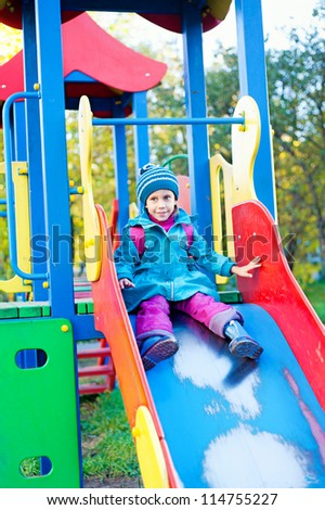 the girl on the playground, slides down a hill