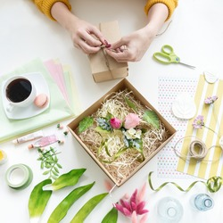 The girl packs the handicrafts to send to the customer who has made an order via the Internet. Online shopping. Manufacturing of artificial flowers and bouquets from foamiran, plastic, fabric, clay.