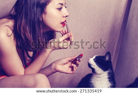 The girl paints lips with lipstick looking in the mirror and watching her cat.