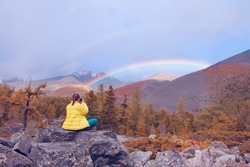 The girl photographs a rainbow on a mobile phone. Beautiful rainbow in the mountains. Travel concept. Selective focus on the girl.