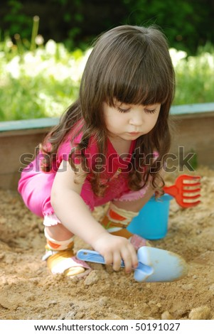 The girl playing to a sandbox. Caucasian the child, park of rest