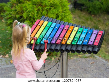 the girl plays a colorful xylophone
