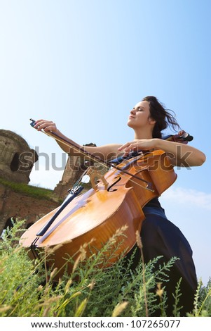 The girl plays a violoncello in the field against a cathedral and sky