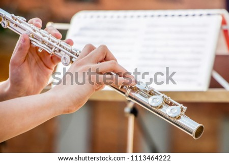 The girl plays the flute. Flute in the hands of the musician during the performance of the musical play #1113464222