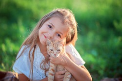 The girl plays with a ginger kitten on the street. Country girl playing with a cat. Child resting on the farm