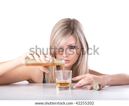 The girl pours whisky from  bottle in  glass on a white background