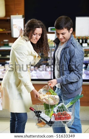 The girl puts in a basket products in shop