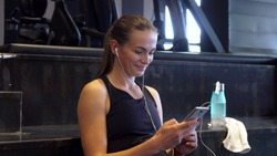 The girl puts on headphones. She includes herself before the sport. She smiles and looks pleased. The girl is sitting on the steps in the gym