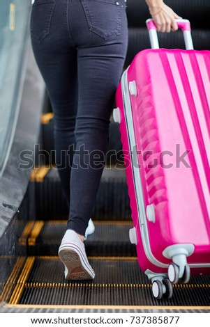 the girl raises a pink suitcase ...